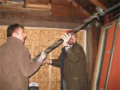 Bill and Todd remove the spring from the garage doorhardware