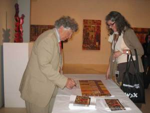 Norman LaLiberte signing a poster for Kimberly Kent